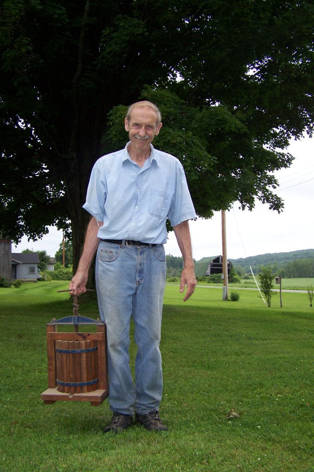 My father with a cider press his family purchased when he was a kid, using proceeds from a bumper crop of potatoes.